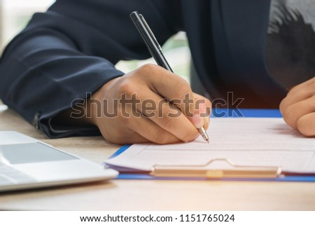 Asian Business man Manager checking and signing applicant filling documents reports papers company application form or registering claim on desk office. Document Report and business busy Concept