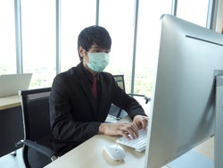 Asian business man or employee wear medical mask is working on his computer desktop.Office personal wok at home to avoid disease of corona virus covid19.