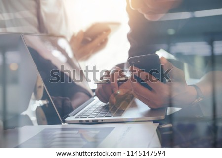 Asian business man, project manager  using mobile phone, working on laptop computer with business report, financial graph on desk in office, business strategy analysis, teamwork concept, close up