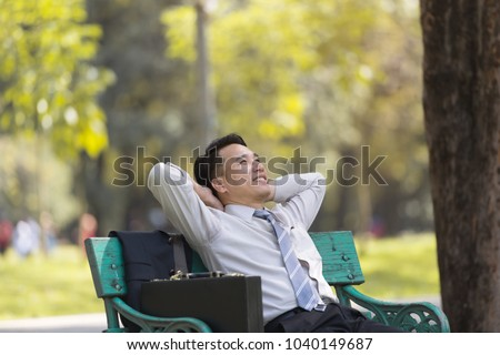 Asian business man relaxing in the park after work. enjoying the shadow of the tree in a sunny day. businessman relieving, rest time concept #1040149687