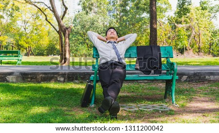 Asian business man relaxing on bench in green natural park, Happy calm smiling successful businessman rest after work outdoor city park, Day dream working Asia people on summer vacation trip