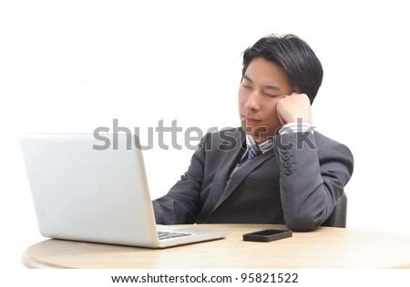 Asian business man resting in front of laptop isolated on white