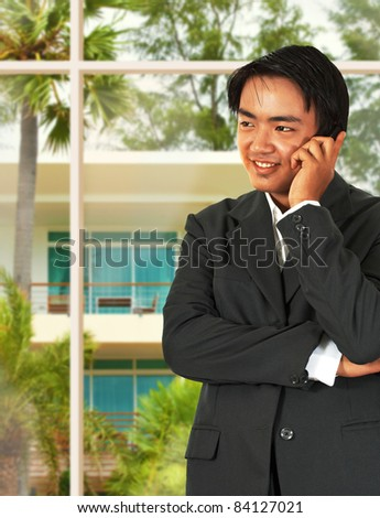 Asian Business Man Talking On The Phone And Standing In His lounge Next To The Garden Window