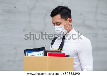 Asian business man wear face mask and he is being fired because of economic downturn due to the covid-19 spread all over the world Stockfoto ©
