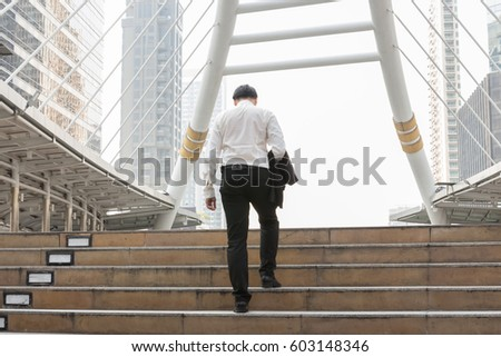 Asian Business men walking on stairs in modern city. #603148346