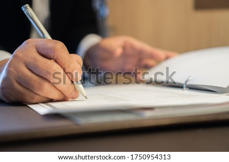 Asian Business people Manager checking and signing applicant filling documents reports papers company application form or registering claim on desk office. Document Report and business busy Concept Photo stock ©