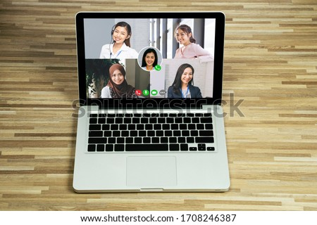 Asian business people team talking to her colleagues in company video conference. Group of business women using laptop for online meeting with video call while working from home.