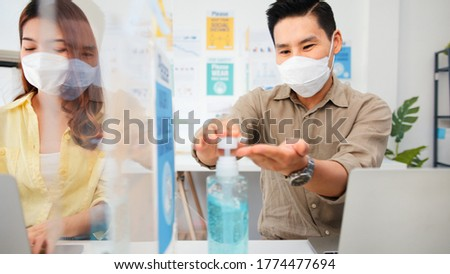 Asian business people wear face mask, wash hand using hand sanitizer, and separated by partition stand. Social distancing at work, new normal office lifestyle after coronavirus lockdown concept
