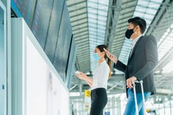 asian business people wear mask face protection business travel checking map and flight schedule at information boarding screen in terminal airport