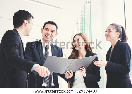 Asian business team discussing work in building hallway