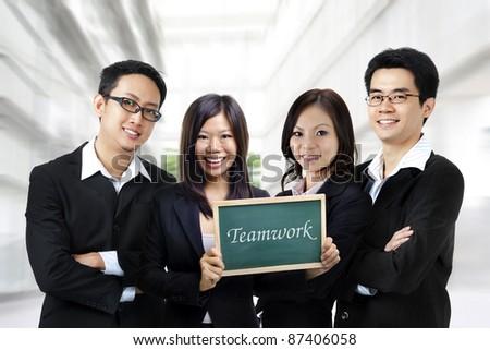 Asian business team on office background, blackboard on hand.