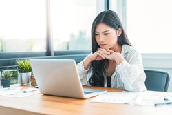 Asian Business woman at home office working using computer laptop technology, small startup business owner entrepreneur, feeling stress anxious impatient noxious from successful business strategy