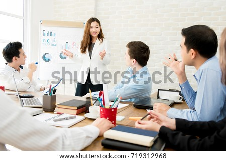 Asian business woman leader in a meeting with her multi-ethnic colleagues at the office presenting sales data or forecast for a project