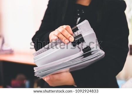 Asian business woman office workers holding are arranging documents of unfinished documents on office desk,Stack of business paper,document management,Businesswoman examining documents #1092924833