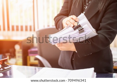 Asian business woman office workers holding are arranging documents of unfinished documents on office desk,Stack of business paper,document management,Businesswoman examining documents