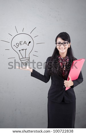 Asian business woman presenting idea. Shot over white board