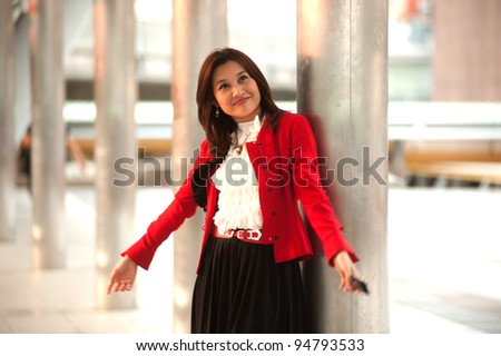 Asian business woman rejoice with arms outstretched .