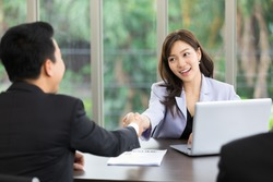 asian business woman shaking hands after a successful job interview at office