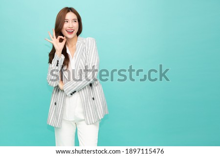 Asian business woman smiling and showing OK sign isolated on green background