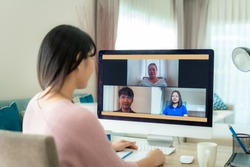 Asian business woman talking to her colleagues about plan in video conference. Multiethnic business team using computer for a online meeting in video call. Group of people smart working from home.