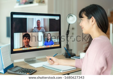 Asian business woman talking to her colleagues about plan in video conference. Multiethnic business team using computer for a online meeting in video call. Group of people smart working from home.  Foto d'archivio ©