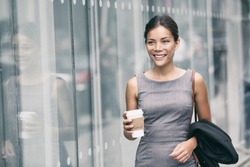 Asian business woman walking going to work drinking coffee to Office building. Successful happy businesswoman commuting in the morning in city street.