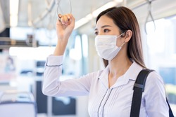 Asian business woman wear surgical mask face to protect herself while commuting in the metro or train
