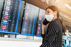 Asian business woman wearing face mask or face shield using cell phone and look up at the flight schedule with copy space, business trip, new normal lifestyle concept, travel bubble, traveling alone.