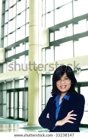 Asian business woman with arms crossed in large office complex