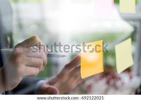 Asian business woman write on post it stick on transparent wall in brainstorm or planning work