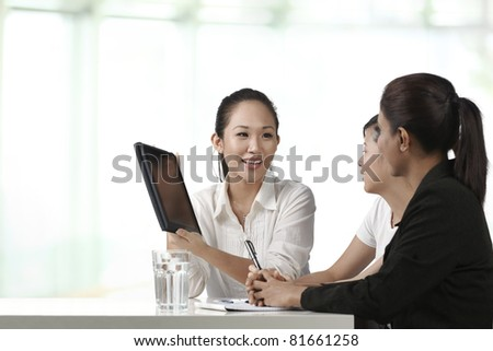 Asian business women having a meeting with a Digital Tablet
