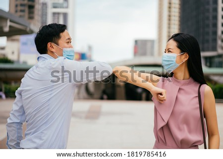 Asian businessman and woman wearing Covid face coverings touching elbows to greet each other, pandemic, Coronavirus, Covid 19