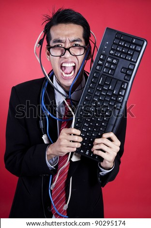 Asian businessman angry holding keyboard isolated on red