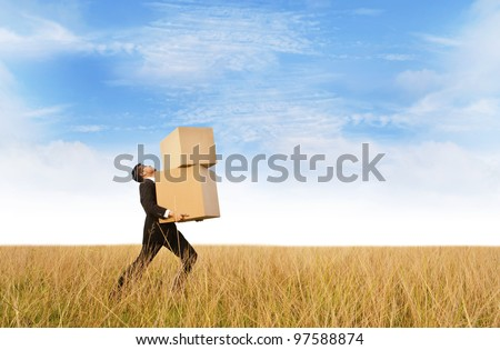 Asian Businessman carrying heavy boxes shot outdoor