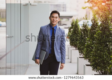 Asian businessman casual holding laptop walking on urban with happiness on a summer's day, Vintage color. #1279643563