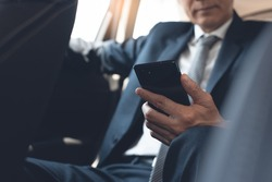 Asian businessman, executive manager reading message or morning news via mobile smart phone application inside a car on backseat, business concept. Corporate man, lawyer going to workplace, close up