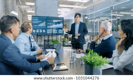 Asian Businessman Gives Report/ Presentation to His Business Colleagues, Pointing at the Results Showing Statistics, Pie Charts and Company's Growth On Wall TV Screen. #1031044276