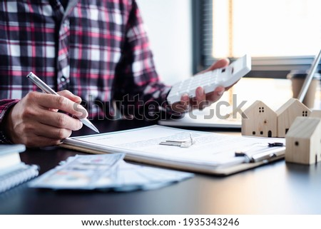 Asian businessman holding a pen to sign a contract to buy or sell a house and land, a contract signing idea.