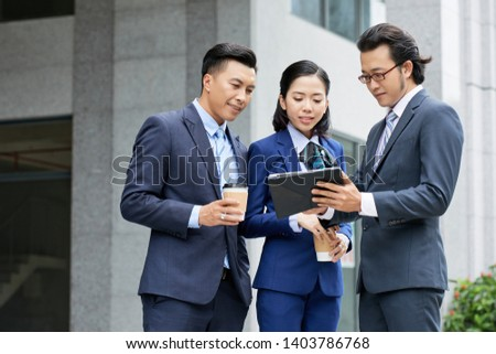 Asian businessman in suit showing online presentation on digital tablet to his colleagues while they standing near the office building outdoors stock photo