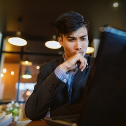 asian businessman in suit working with laptop