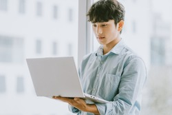 Asian businessman is using laptop to work by window