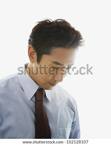 Asian businessman looking down