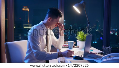 asian businessman overtime work and feel eye tired in the office
