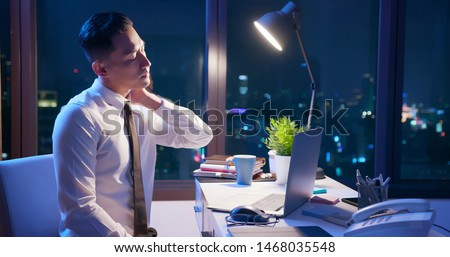 asian businessman overtime work and feel neck pain in the office