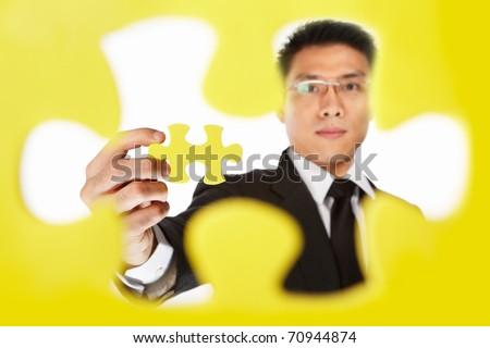 Asian businessman showing the last piece of puzzle, over white background