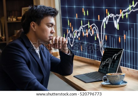 Asian Businessman sitting and using computer laptop showing trading graph beside the windows glass over the stock exchange trading graph screen background, Business financial and forex concept