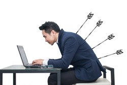 Asian Businessman sitting at a desk using a laptop with arrow stabbing his back,Business concept
