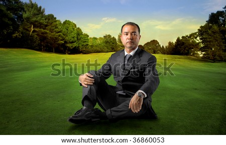 asian businessman sitting in a beautiful park