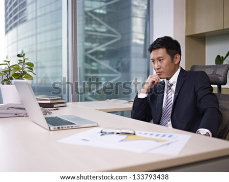 asian businessman sitting in office, looking depressed.
