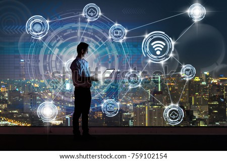 Asian businessman standing and using the laptop showing Wireless communication connecting of smart city Internet of Things Technology over the cityscape background, technology and innovation concept #759102154